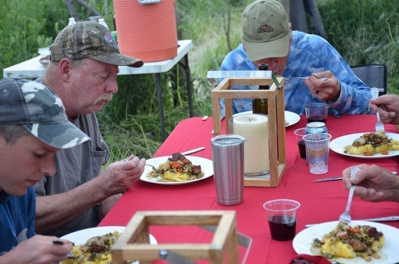 men eating food at dinner on fly fishing trip